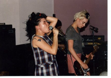 A young Kathleen Hanna, wearing a plaid skirt and singing